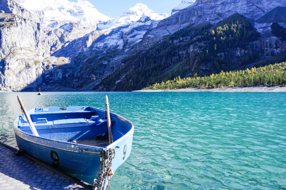 boat lake mountain row blue green water snow mountain alps swiss clear grass