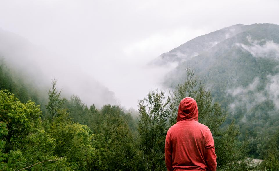 mountain highland cloud sky summit ridge landscape nature valley hill fog view travel outdoor people man guy alone climbing hiking trek adventure millennials red hoodie
