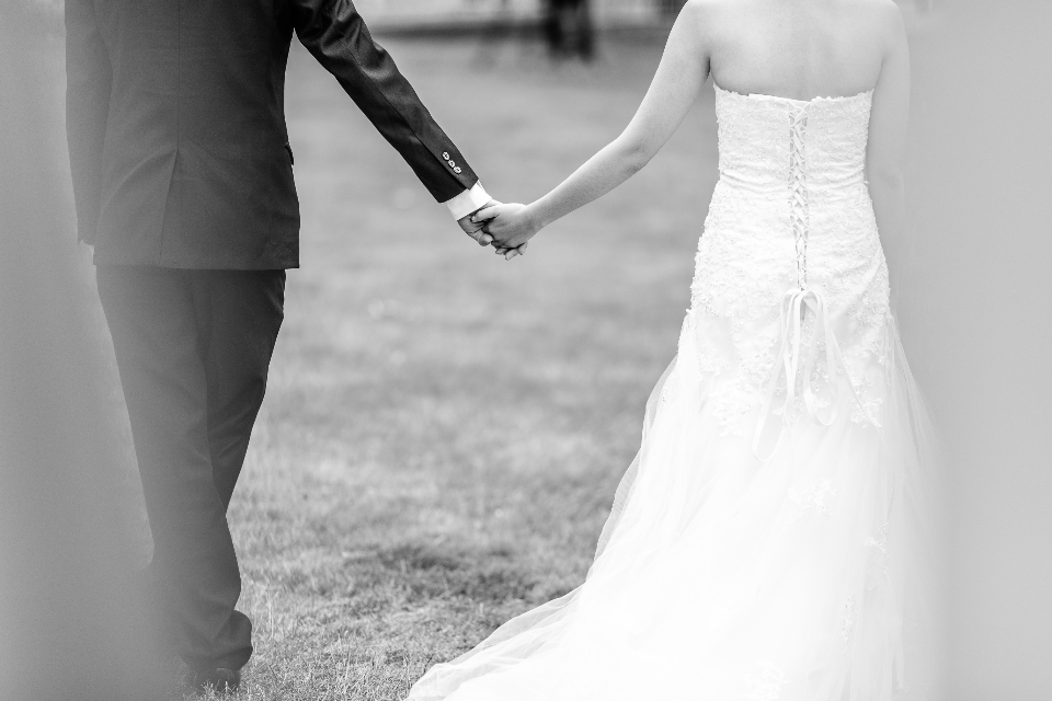 bride groom wedding holding hands married walk grass black & white white dress man woman love romantic