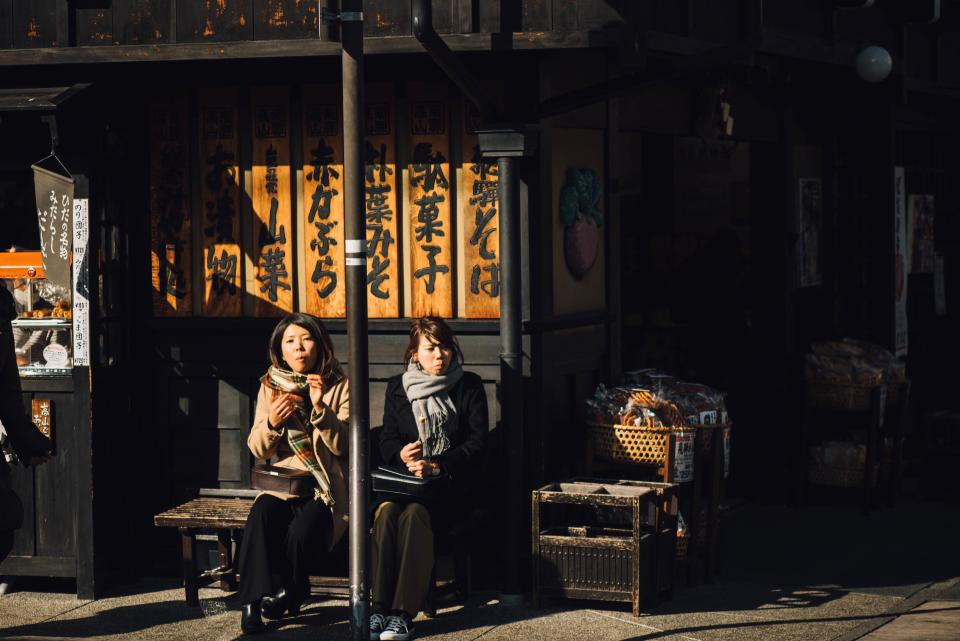 people woman lady sister post bench steel wooden building old establishment store food sunshine day shadow sidewalk