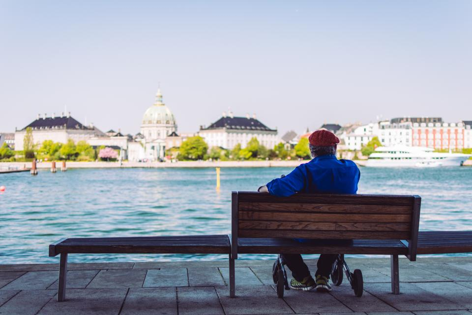 sea ocean water waves nature buildings city people old man sitting alone wooden bench waiting