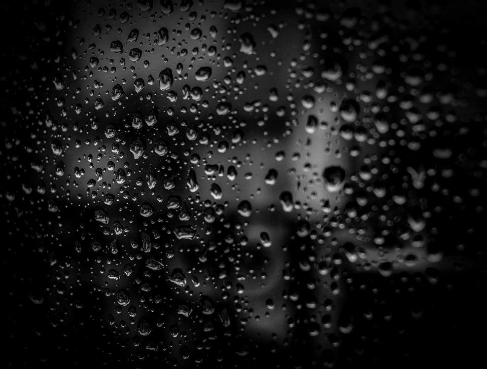 black dark glass window wet rain water drops