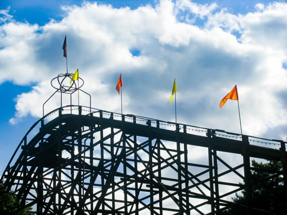 rollercoaster amusement park fun ride flags sky clouds sunshine silhouette shadow