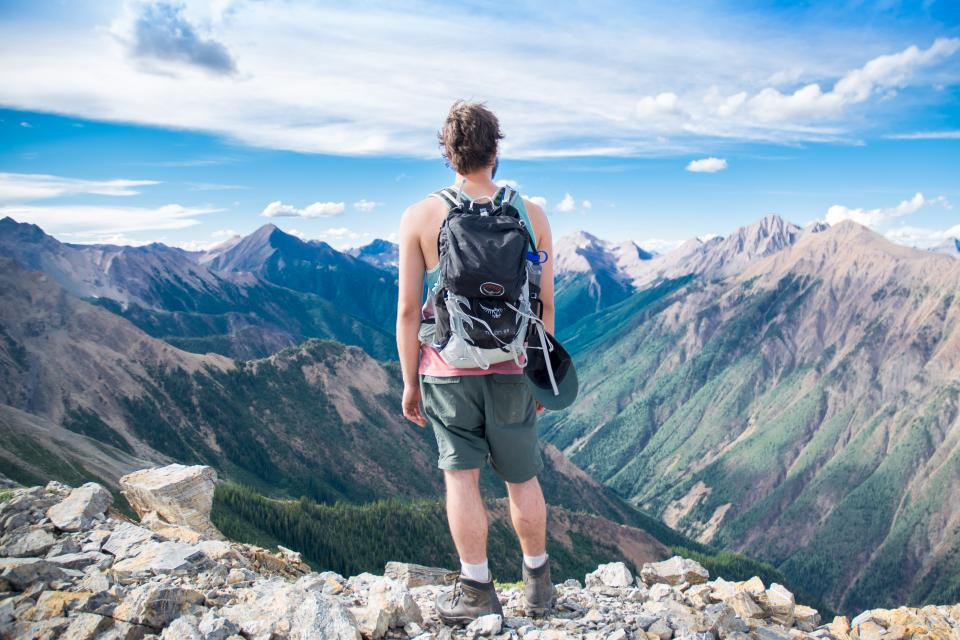 guy man male people back contemplate fashion style view mountains summit peaks rocks lush vegetation majestic sky clouds travel hike climb fitness