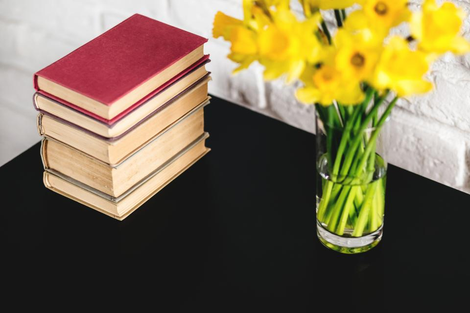 yellow flower vase table books blur