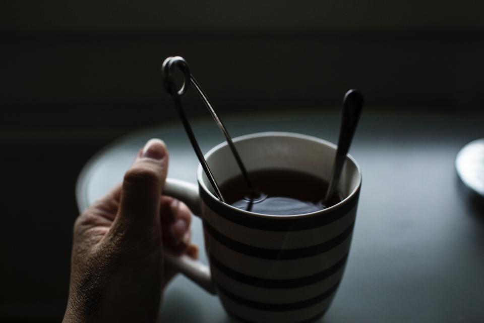 dark coffee drink table spoon cup hand blur