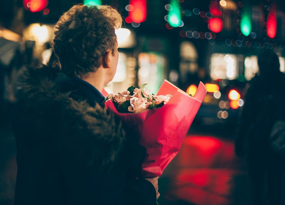 man flowers blur bokeh lights cold jacket road night bouquet people