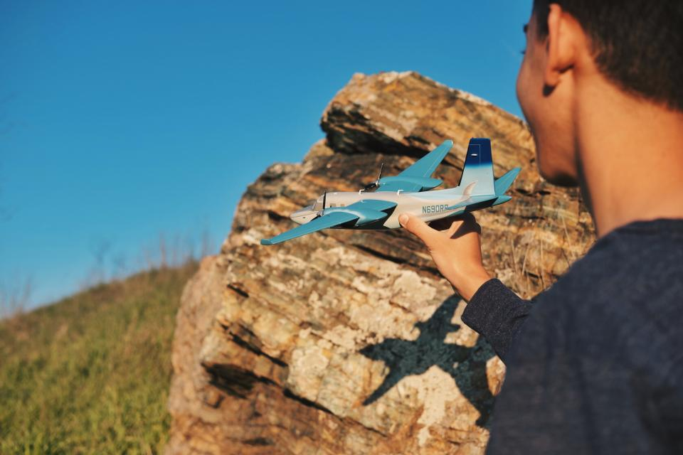airplane airline toy blue sky green grass rocks cliff people man