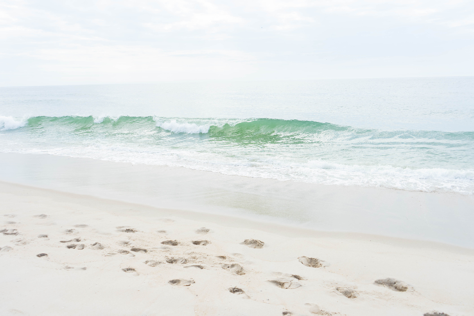 beach sand waves wet ocean saltwater nature shore coast foam water tide footprints sky foot print trail