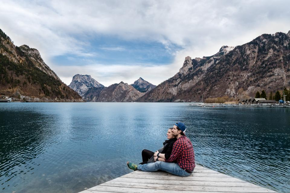 couple man woman girl guy mountains love people outdoor happy smile sweet view sitting river water date wooden clouds sky cap lookup