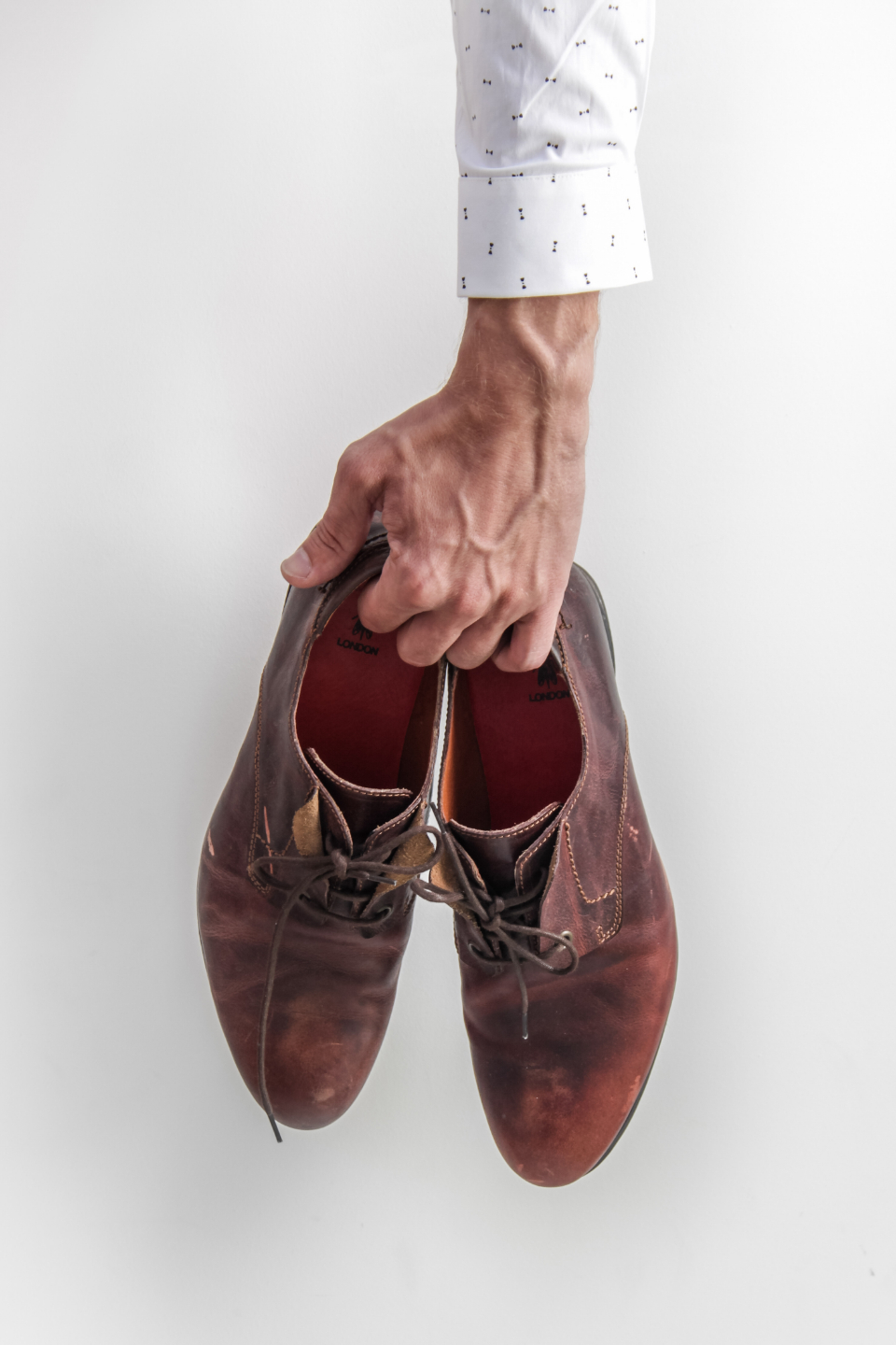 man holding shoes